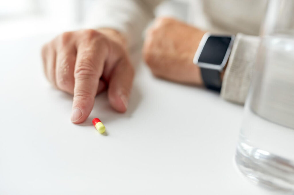 close up of old man hand with pill and smart watch P89VFXF 1