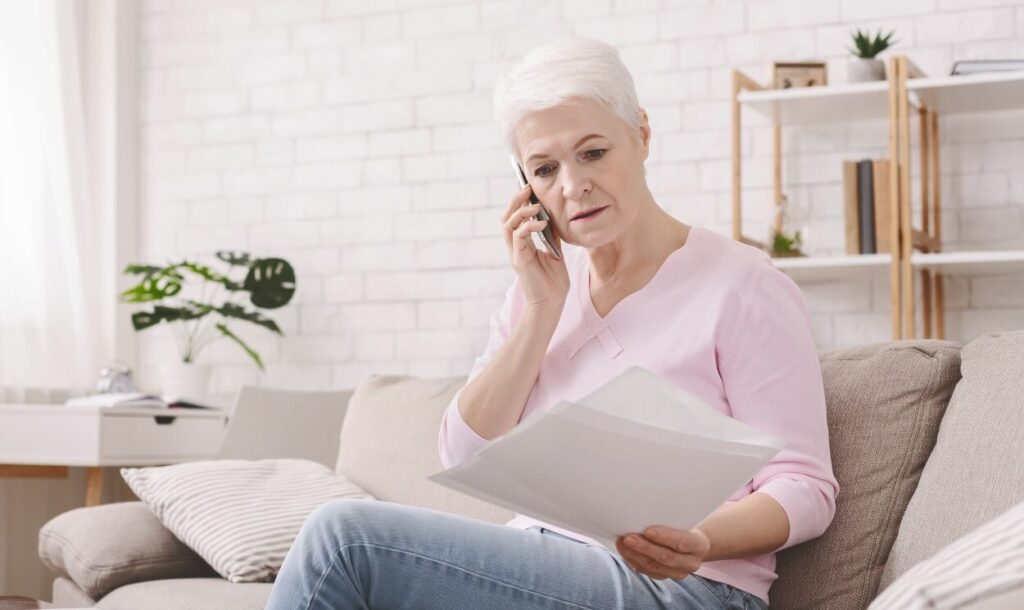 shocked retired woman listening to bank agent with GGUPGWX